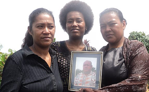 Mere Tavo (middle) flanked by two of her four siblings with a framed photo of their father, Kelepi Bainivalu who passed away one year ago today at the age of 56. Photo: Courtesy of: Mereseini Tavo